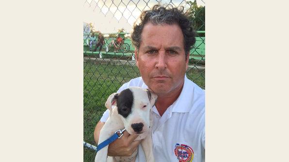 Coach Mac holding a puppy